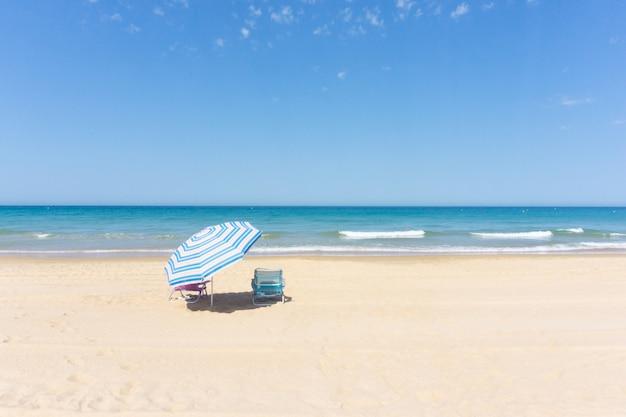 Guarda-chuva e duas espreguiçadeiras na praia