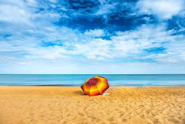 Guarda-chuva laranja na praia de areia dourada em um dia ensolarado, mar azul ao fundo
