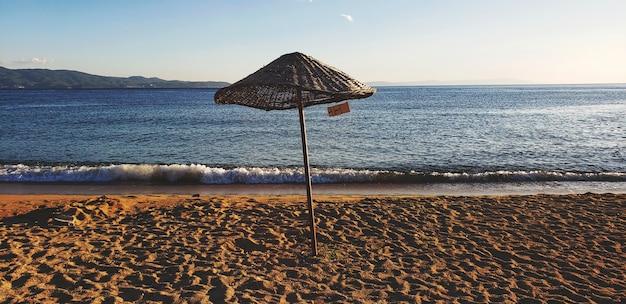 Guarda-chuva na praia e céu azul