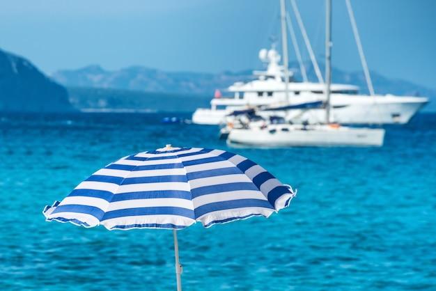 Guarda-chuvas coloridos na praia tropical com mar azul e iates como pano de fundo
