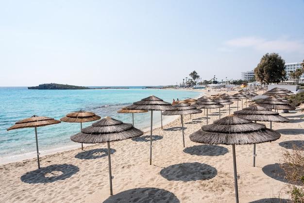 Guarda-chuvas de praia de reed, guarda-sóis contra o céu azul na praia.