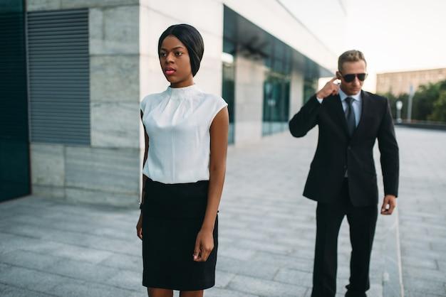 Guarda-costas pessoal em óculos escuros e mulher de negócios negra.