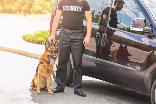 Guarda de segurança com cachorro perto do carro, ao ar livre