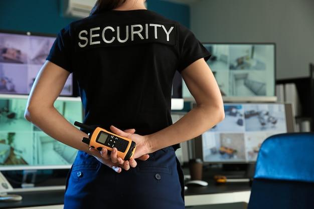 Guarda de segurança com transmissor de rádio portátil monitorando câmeras de cftv modernas na sala de vigilância