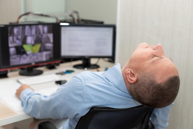 Guarda de segurança dormindo no local de trabalho em um trabalho chato de sala de vigilância