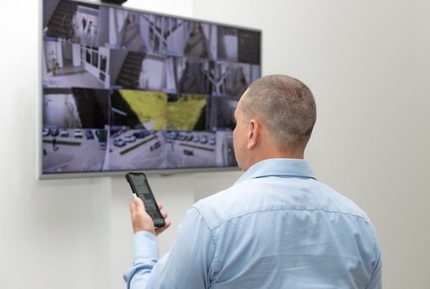 Guarda de segurança em frente a um grande monitor cctv