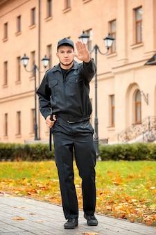 Guarda de segurança masculino com bastão de polícia na rua da cidade