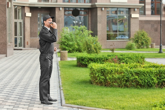 Guarda de segurança masculino com rádio portátil, ao ar livre