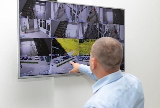 Guarda de segurança monitorando sistema de segurança de vigilância em grande monitor de cftv