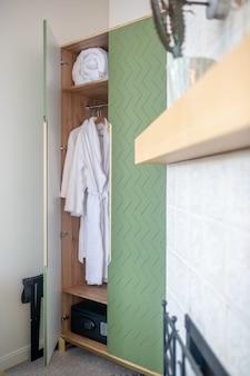 Guarda-louça. guarda-roupa verde aberto com roupão branco e cobertor enrolado na sala de estar