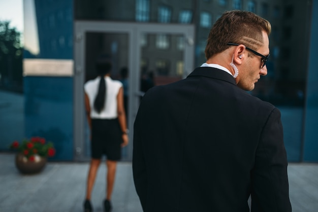 Guarda pessoal em óculos de sol e fone de ouvido de segurança, vista traseira, mulher negra de negócios