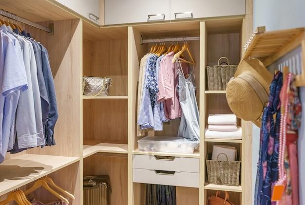 Guarda-roupa de madeira moderno com roupas penduradas no trilho em pé no armário
