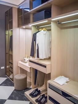 Guarda-roupa de madeira moderno com roupas penduradas no trilho em pé no interior do design do armário