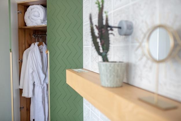 Guarda-roupa, quarto. roupões de banho brancos e cobertor em armário verde aberto no quarto e prateleira de parede com vaso de flores e espelho