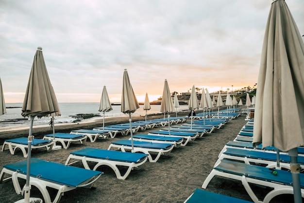 Guarda-sóis e assentos em negócios fechados na praia após um dia de sol e férias conceito de lazer ao ar livre