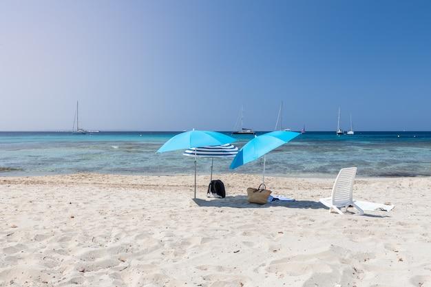 Guarda-sóis solitários na areia branca da bela praia de ses salines na ilha de ibiza. ilhas baleares, espanha