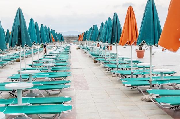 Guarda-sóis verdes e laranja e espreguiçadeiras perto da piscina no resort de verão