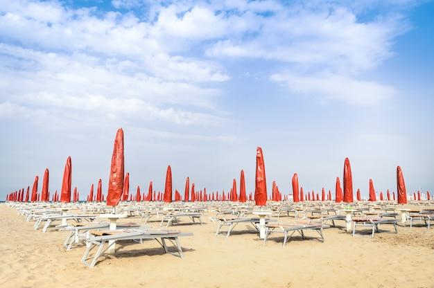 Guarda-sóis vermelhos e espreguiçadeiras na praia de rimini - visão geral do verão italiano no início da temporada