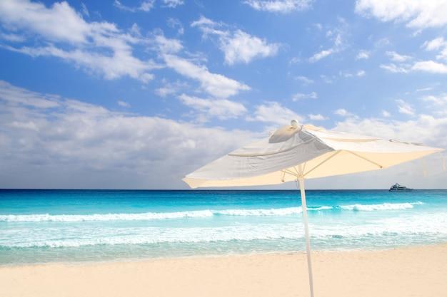Guarda-sol branco parasol na praia do caribe turquesa