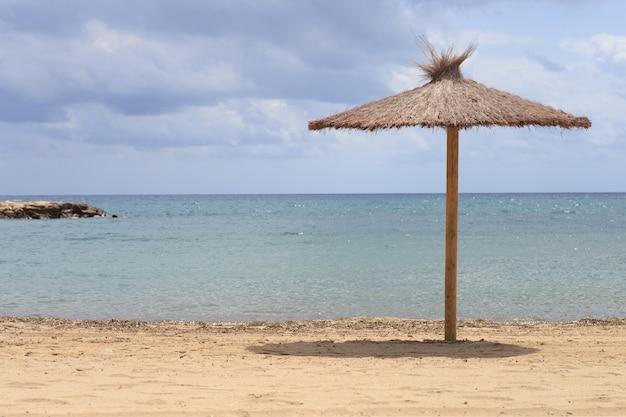 Guarda-sol de folhas secas perto do mar. conceito de férias de viagens.