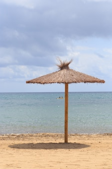Guarda-sol de folhas secas perto do mar.