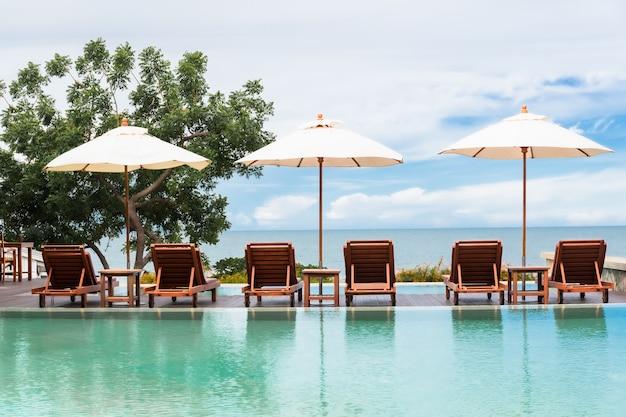 Guarda-sol e cadeiras de praia ao lado da piscina com vista para o mar.