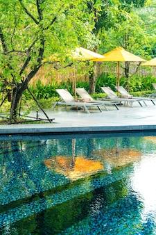 Guarda-sol e decoração da cama da piscina ao redor da piscina em hotel resort