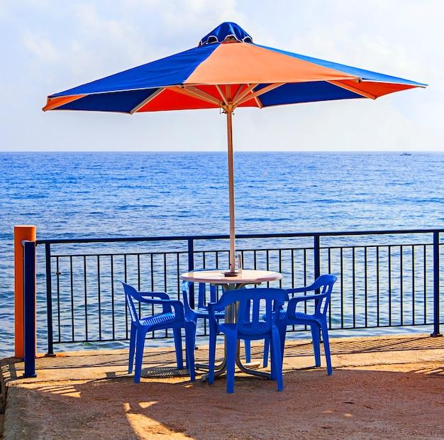 Guarda-sol e mesa no café às margens do mar azul