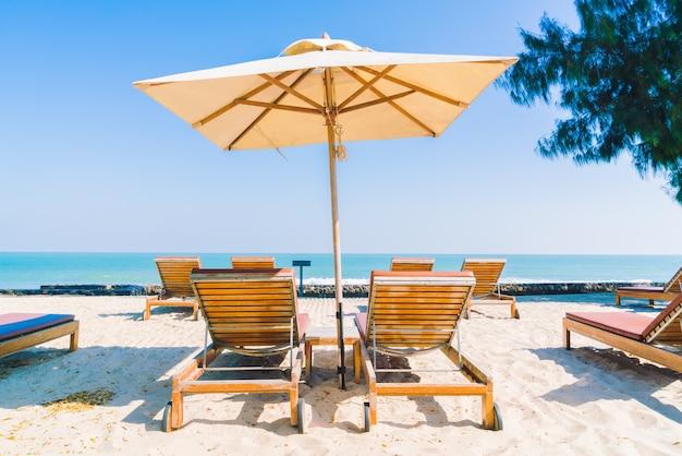 Guarda-sol piscina e cadeira na praia
