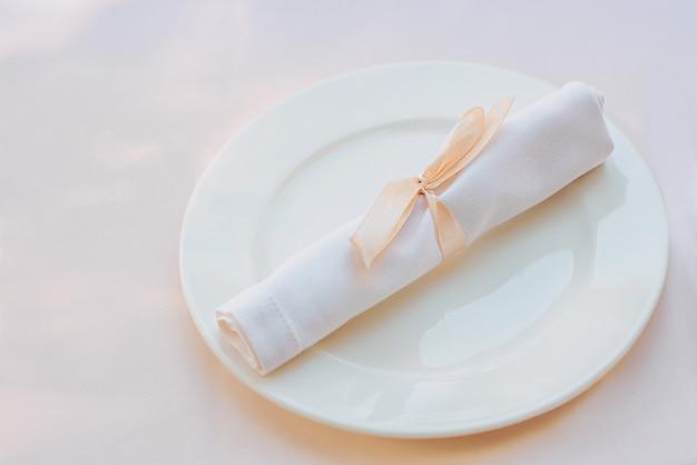 Guardanapo branco no prato na mesa conceito de almoços de comida de talheres