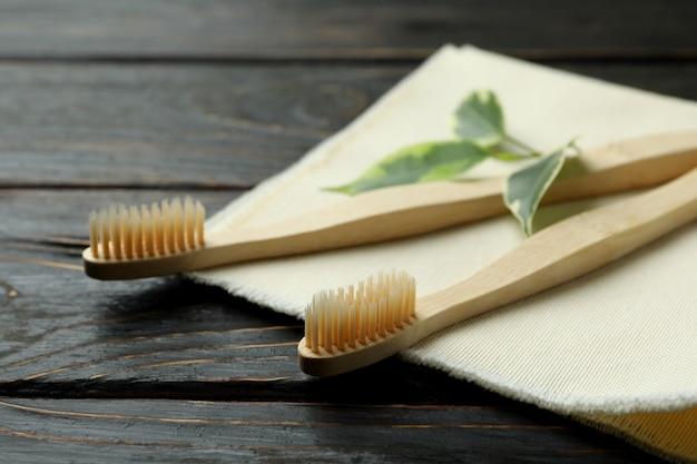 Guardanapo com escova de dentes ecológica e galho em fundo de madeira