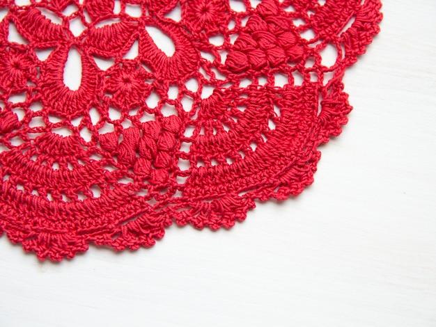 Guardanapo de crochê vermelho sobre vista de mesa de madeira branca