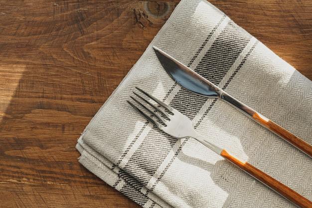Guardanapo de linho listrado na mesa de madeira com utensílios de cozinha fechar