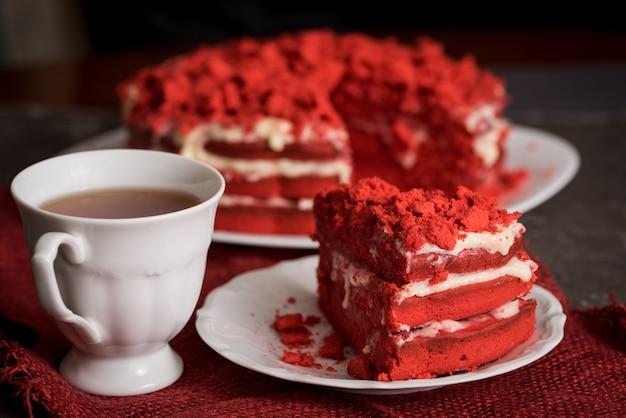 Guardanapo de lona de bolo de veludo vermelho sobre um fundo cinza escuro concreto