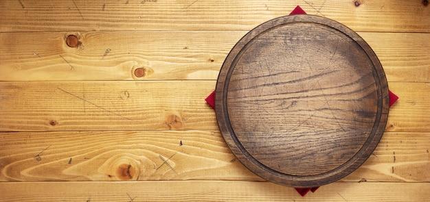 Guardanapo de pano e tábua de cortar pizza na textura de fundo de madeira
