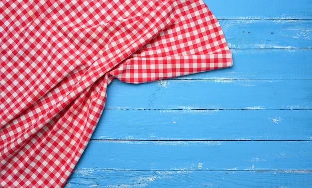 Guardanapo dobrado de algodão vermelho e branco sobre fundo azul de madeira, vista de cima, espaço de cópia