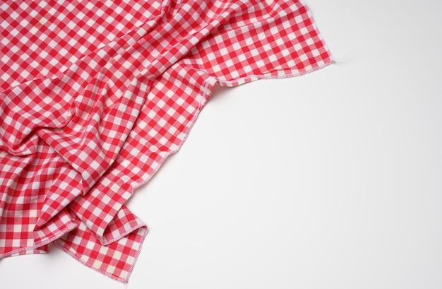 Guardanapo dobrado de algodão vermelho xadrez branco sobre fundo branco, vista de cima, espaço para cópia