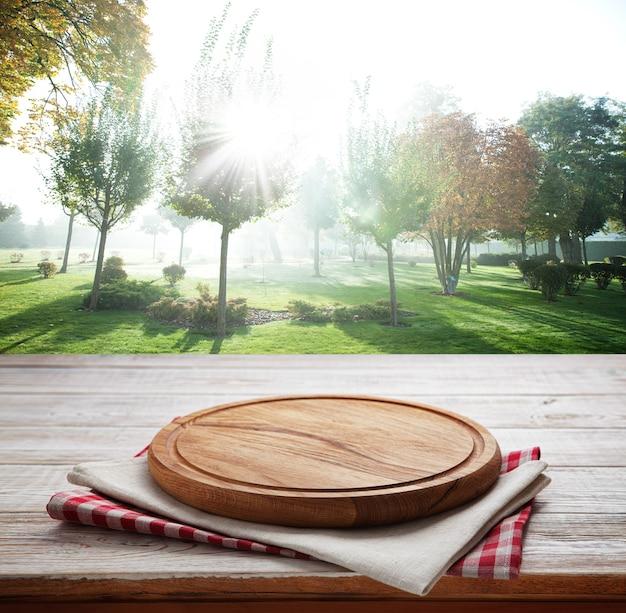 Guardanapo e tábua para pizza na mesa de madeira. paisagem de verão.