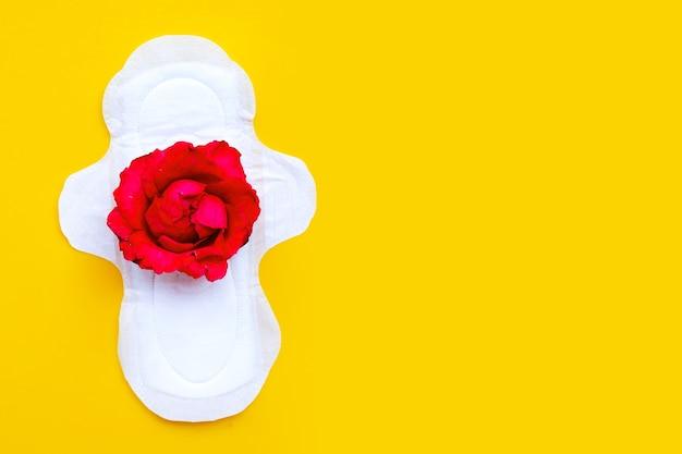 Guardanapo higiênico branco com rosa vermelha na superfície amarela
