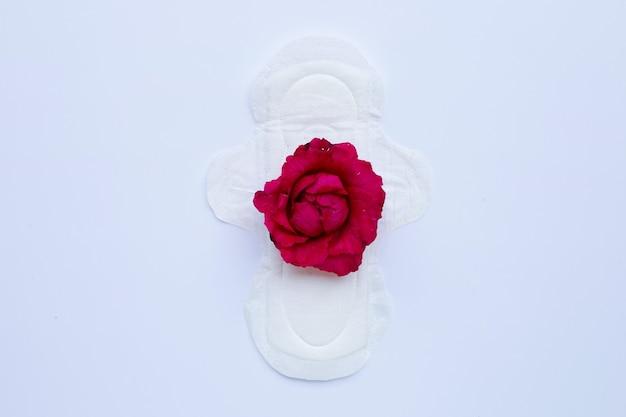 Guardanapo higiênico branco com rosa vermelha na superfície branca