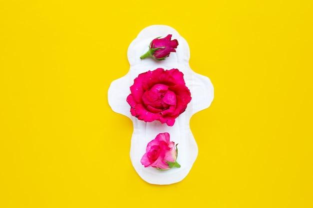 Guardanapo higiênico branco com rosas vermelhas na superfície amarela