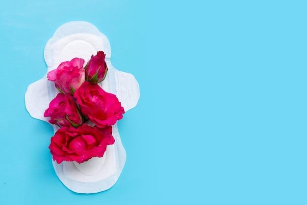 Guardanapo higiênico branco com rosas vermelhas na superfície azul