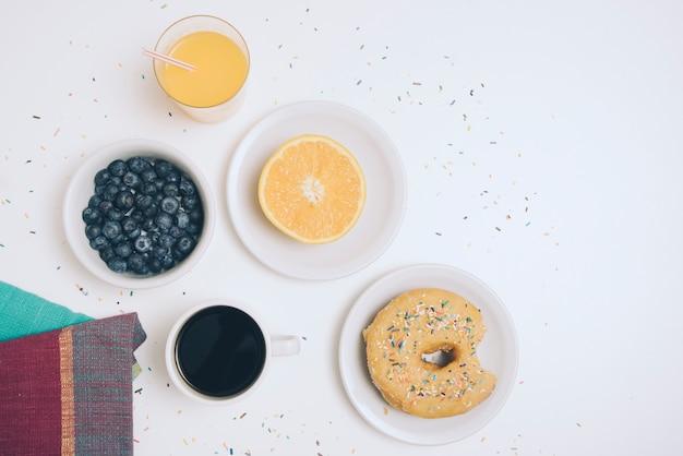 Guardanapo; mirtilo; copo de suco; meia laranja; xícara de café e donut em pano de fundo branco