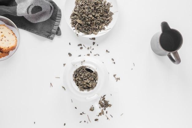 Guardanapo; pão com folhas de chá e bule de chá em pano de fundo branco