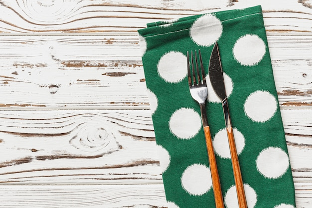 Guardanapo verde de bolinhas na mesa de madeira resistiu