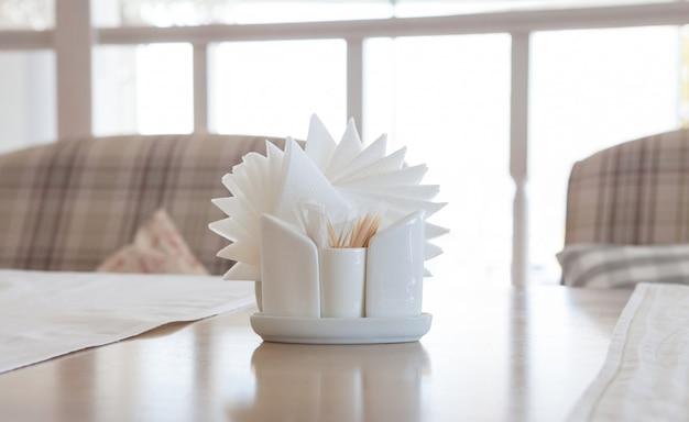 Guardanapos brancos em titulares na mesa de madeira, close-up