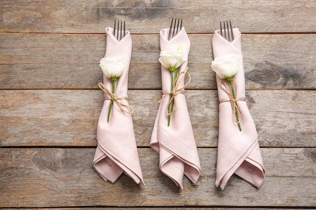Guardanapos com decoração floral e talheres na mesa de madeira