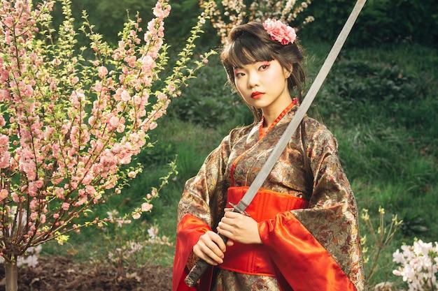 Gueixa bonita no quimono com espada samurai