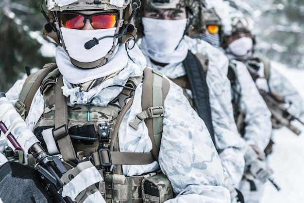 Guerra das montanhas árticas de inverno. ação em condições de frio. esquadrão de soldados com armas na floresta em algum lugar acima do círculo polar ártico