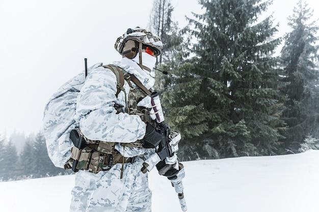 Guerra das montanhas árticas de inverno. ação em condições de frio. soldado com armas em uma floresta em algum lugar acima do círculo polar ártico. perfil, vista lateral